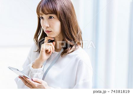 スマホを見ながら何かを考える女性 74381819