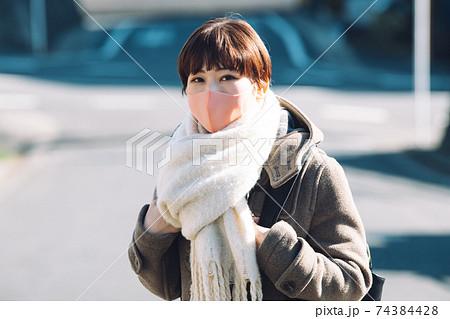 コートとマフラーとマスクを着用した冬の女性 74384428