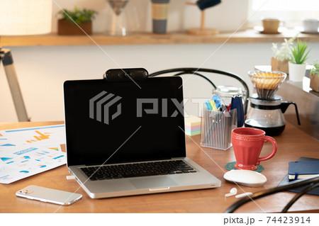 ダイニングテーブルのウェブカメラ付きのノートパソコン 74423914