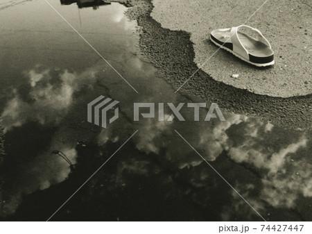 水たまりに映る空とサンダル:モノクロ 74427447