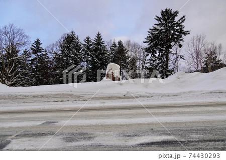 雪に埋もれた石勝樹海ロードの石碑 74430293