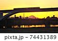 足立区と荒川区を繋ぐ扇大橋を渡る舎人線と富士山と荒川遊園地の観覧車の観える冬の夕暮れの風景  74431389