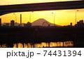 足立区と荒川区を繋ぐ扇大橋を渡る舎人線と富士山と荒川遊園地の観覧車の観える冬の夕暮れの風景  74431394