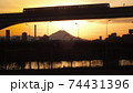 足立区と荒川区を繋ぐ扇大橋を渡る舎人線と富士山と荒川遊園地の観覧車の観える冬の夕暮れの風景  74431396
