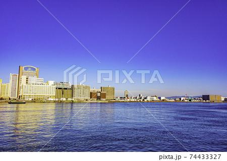 青空を背景に対岸沿いに建つホテルやビル等の建物見た静かな朝の海の風景 74433327