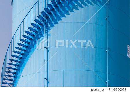 工場内の青い円筒タンクに設置されている螺旋階段 74440263