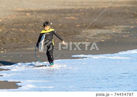湘南の砂浜でサーフィンをし終わった小学生の男の子 74454797