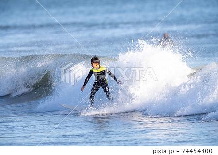 湘南でサーフィンをする小学生の男の子 74454800