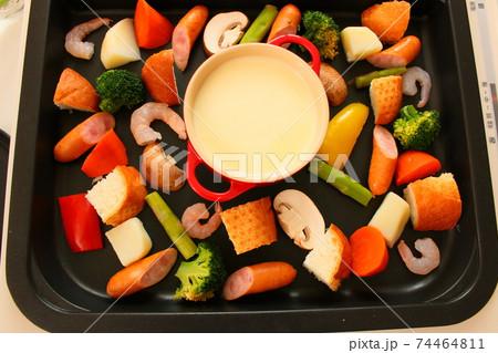 ホットプレートでチーズフォンデュをする家族の晩ご飯風景 74464811