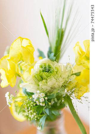 グラスに活けたラナンキュラスと黄色い花 74475543