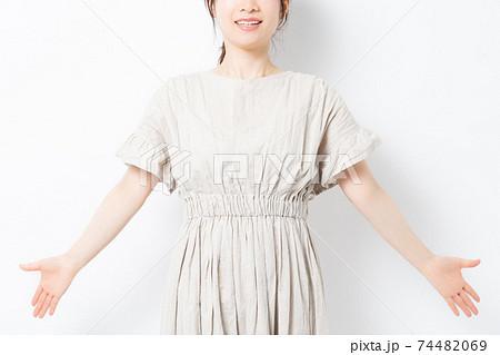 白背景の前に立って深呼吸をする若い女性 74482069