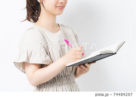 白背景の前に立ってノートにメモを書く若い女性 74484207