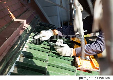 新しく漆喰を塗り直す屋根職人 74496180
