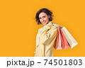 Young adult girl with shopping bags looking at camera 74501803