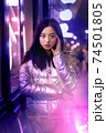 Neon Style. Asian girl in glossy jacket standing on the street in fluorescent violet lights touchign head concerned 74501805