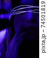 Young adult millennial woman in bright neon light, touching her lips with fingers 74501819
