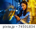 Neon Style. Asian girl in glossy jacket with wireless earphones standing on the street in fluorescent yellow lights listening to music browsing smartphone smiling cheerful 74501834