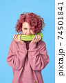 Pretty girl with pink curly hair in pink casual hoodie biting bunch of fresh celery 74501841