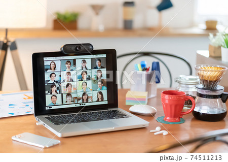 ダイニングテーブルに置いてあるパソコンのweb会議の画面 74511213