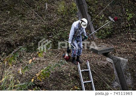 法面の草刈りを終えて電動草刈機を片付ける植木職人 74511965