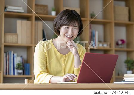 ノートパソコンで作業をする若い女性  74512942