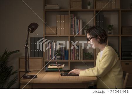 ノートパソコンで作業する若い女性 夜イメージ 74542441