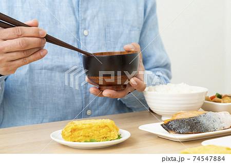 和食を食べる男性 味噌汁 74547884