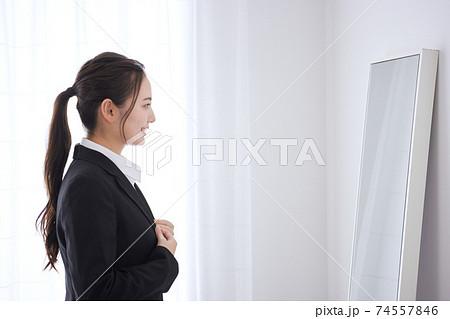 鏡の前で身支度をする若いビジネスウーマン  74557846