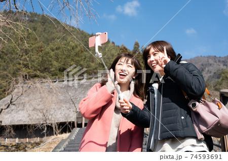 冬の西湖根場をバックに記念撮影する二人の女性 74593691