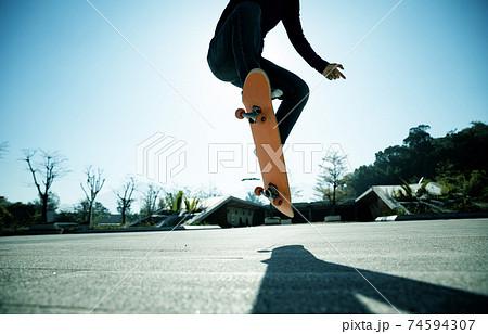 Asian woman skateboarder skateboarding outdoors 74594307