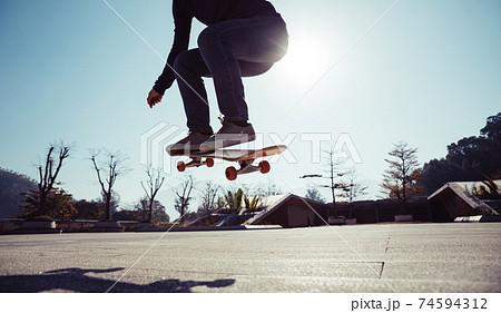 Asian woman skateboarder skateboarding outdoors 74594312