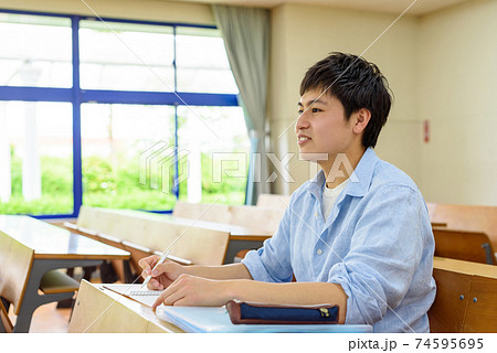 大学の教室で講義を受ける男子大学生 自然光 74595695