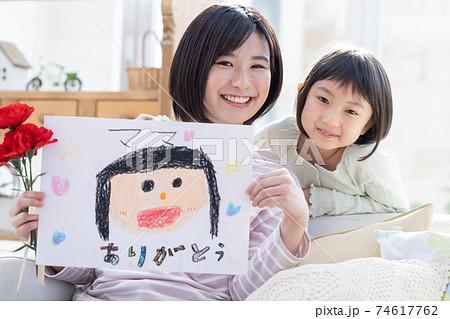 母の日カーネーションと似顔絵を貰ったママと女の子のポートレート 74617762