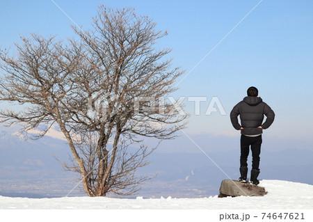 雪山で成功者のような立ち姿の男性 74647621