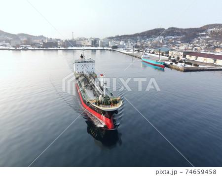 冬の北海道室蘭市室蘭港から離岸、出港する貨物船の朝の風景を撮影 74659458