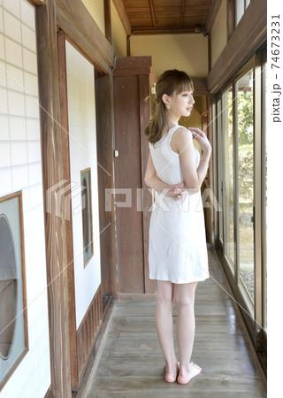 古民家の廊下に立つ白いキャミソールを着た若い女性 74673231