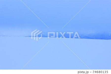 【北海道上富良野町の冬】丘の稜線と雲で隠れる十勝岳連邦 1月 74680135