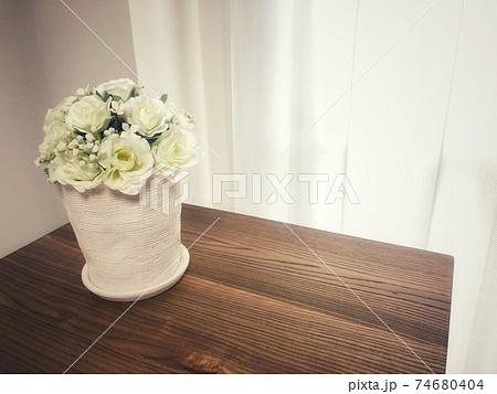 白い部屋の木製テーブルの上に置かれた白い薔薇の植木鉢がある風景 74680404