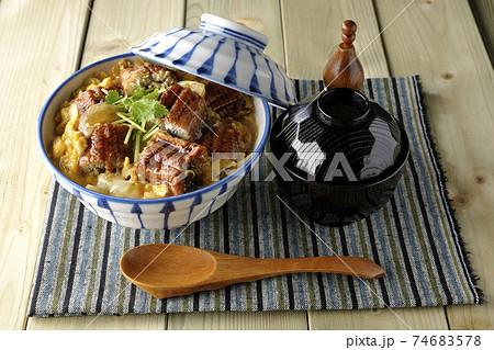 ランチョンマットの上の鰻蒲焼きを卵でとじたうな玉丼とお吸い物のセットと木製スプーン 74683578