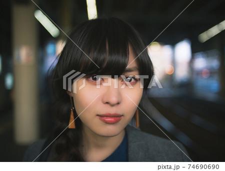 駅のホームにて カメラ目線の三つ編みの女性の顔のアップ 74690690