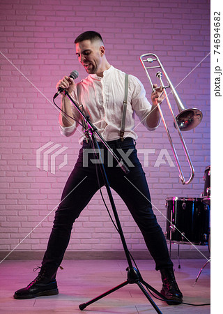 the man with a trombone in a club in neon light 74694682