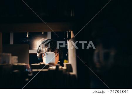 夜にスマホで音声コンテンツを楽しむ男性 74702344