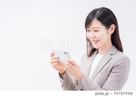 スマホで動画視聴またはオンラインゲームを楽しむビジネスウーマン 74707499