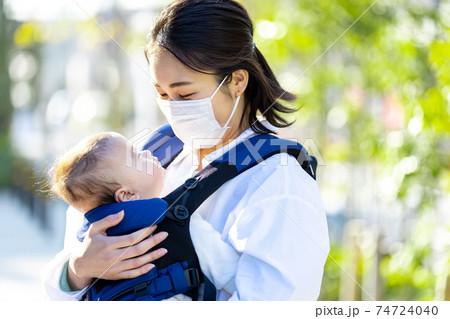 マスクをつけながら抱っこ紐で歩くママと子供 74724040