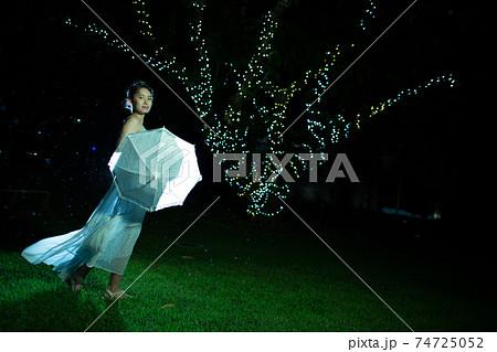 雨模様の夜の公園に立つハーフの女性 74725052