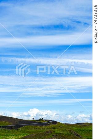 【アイスランド】爽やかな青空の下でハイキングする風景(縦) 74733326