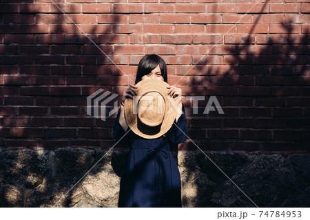 麦わら帽子を持って口元を隠しているロングヘアの女性 カメラ目線 74784953