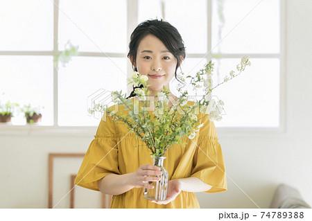 コデマリをいけた花瓶を持った若い女性 74789388