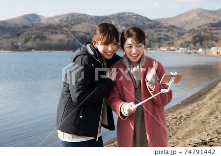 冬の山中湖畔で記念撮影する二人の女性 74791442