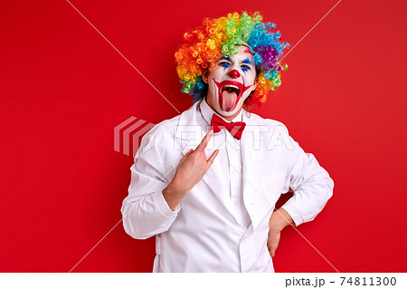 optimistic clown harlequin with rock and roll gesture isolated on red background 74811300